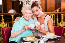 elder drinking tea with caregiver